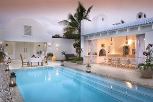 Beautiful poolside photo at sunset, surrounded by glittering lanterns, at Santorini Mozambique