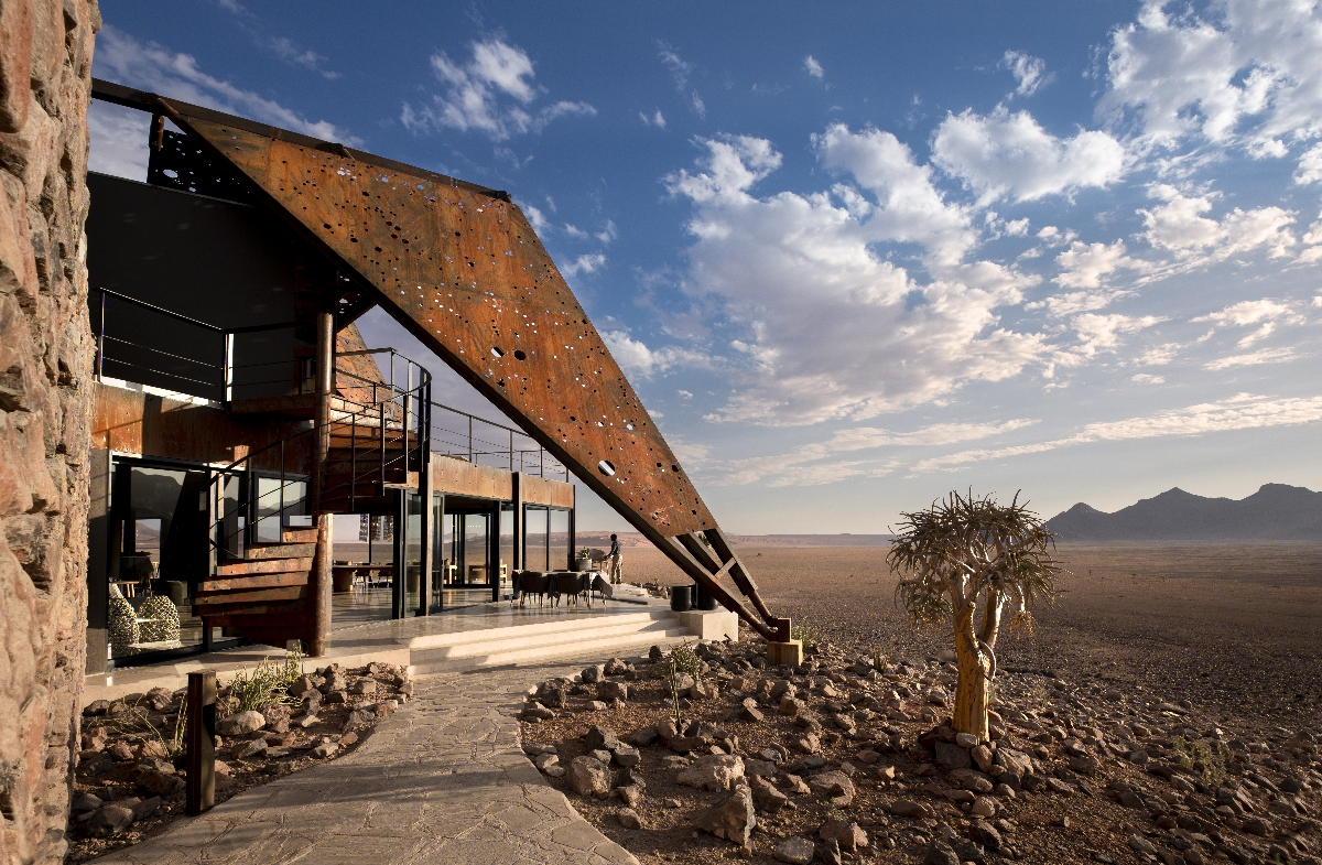 Exterior of &Beyond Sossusvlei Desert Lodge in Namibia surrounded by endless desert and blue skies