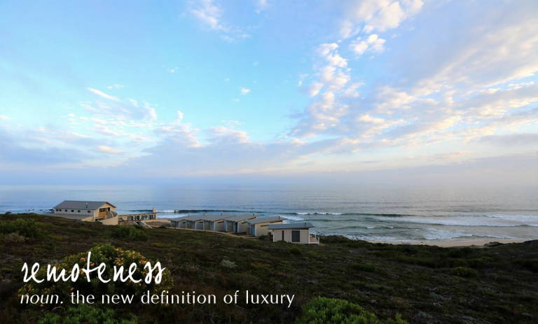 Lekkerwater Beach Lodge at sunset with the ocean beyond the fynbos landscape