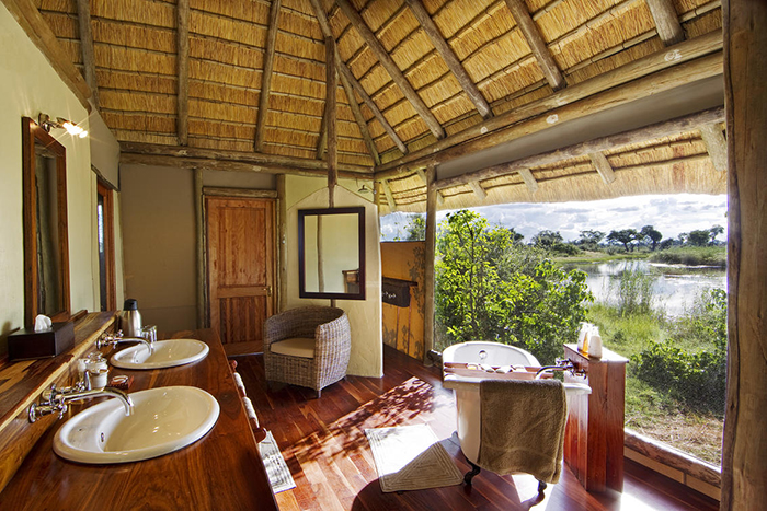 A light and airy bathroom with endless views out over the floodplains at Kwando Lagoon Camp in Botswana